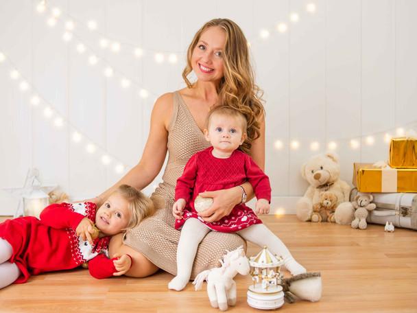Madre con hijas en Fotografías de Sesión de Navidad, mujer, niña y bebé con sweater rojo de navidad, Fotografías de Sesión de Navidad, Christmas Photo Session, Luces de Navidad en decorado dorado de navidad, abrazo familiar