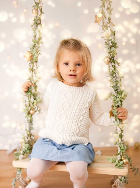 Fotografías de Sesión de Navidad, niña en columpio navideo, niña rubia de ojos claros sonriendo posando, Fotografías de Sesión de Navidad, Christmas Photo Session, Luces de Navidad en decorado dorado de navidad