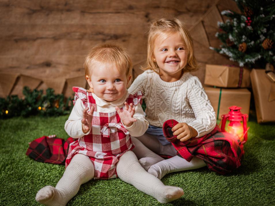 Fotografías de Sesión de Navidad, bebe y niña mirando con farol, niña y bebe rubia de ojos claros posando, Fotografías de Sesión de Navidad, Christmas Photo Session, bebé con farol, nieve. Niñas protegiéndose de la nieve