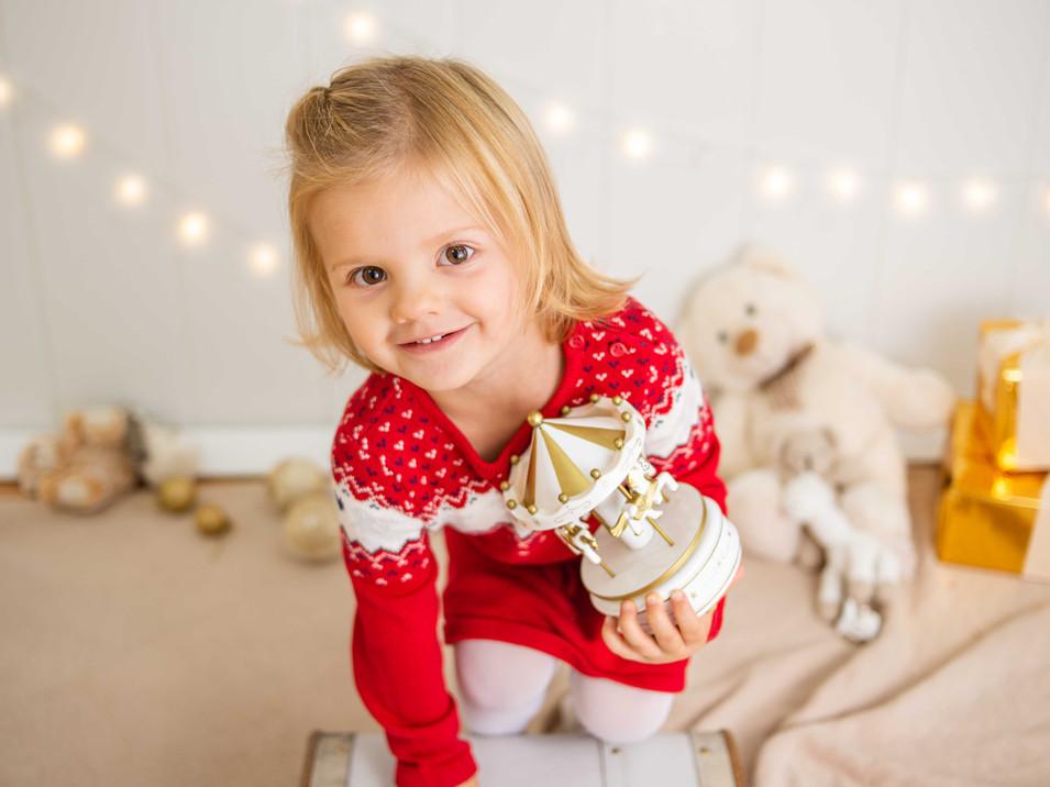 Fotografías de Sesión de Navidad, niña con sweater rojo de navidad, niña rubia de ojos claros sonriendo posando, Fotografías de Sesión de Navidad, Christmas Photo Session, Luces de Navidad en decorado dorado de navidad con calesita de caballos