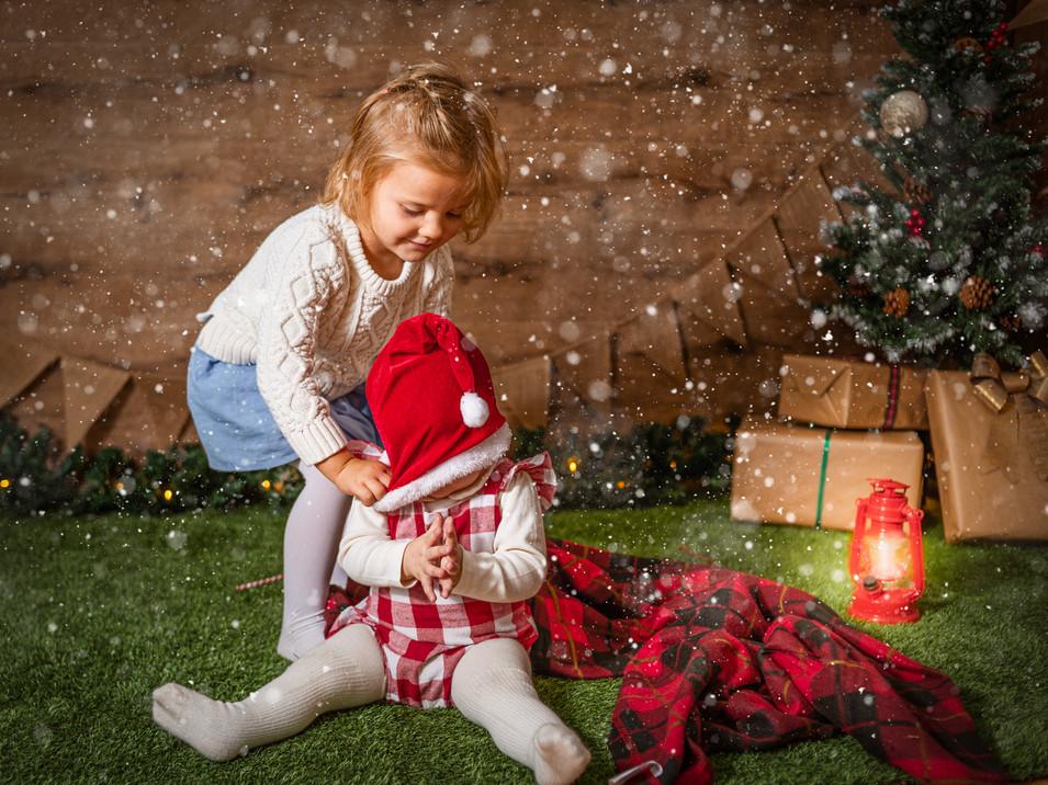 Arbol de Navidad, Fotografías de Sesión de Navidad 2020, bebe y niña jugando con gorro navideño, niña y bebe rubia de ojos claros posando, Fotografías de Sesión de Navidad, Christmas Photo Session, bebé con farol, nieve. Niñas en la nieve