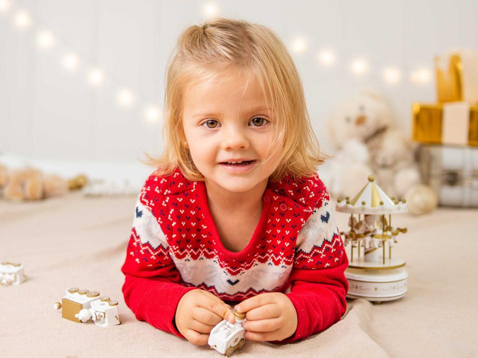 Fotografías de Sesión de Navidad, niña con sweater rojo de navidad, niña rubia de ojos claros sonriendo posando, Fotografías de Sesión de Navidad, Christmas Photo Session, Luces de Navidad en decorado dorado de navidad