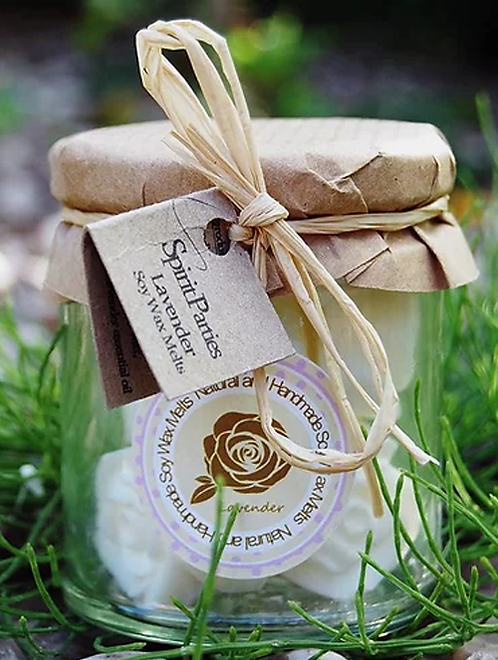 Lavender natural wax melts in a jar with a spiritual logo and spirit parties tag against a natural holistic grass background