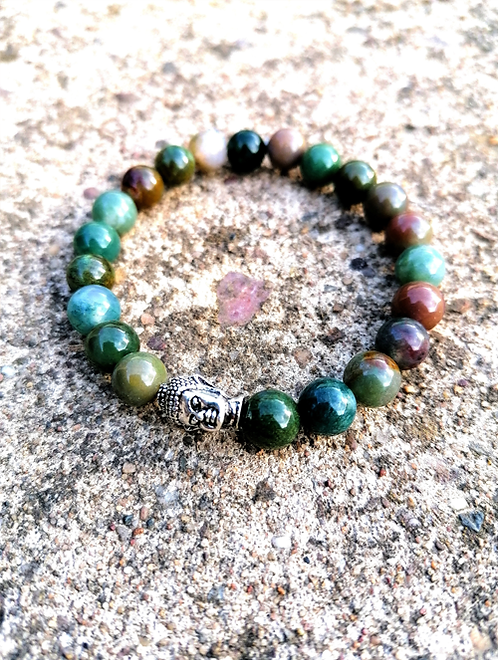 An Indian Agate Buddha spiritual bracelet on a paved holistic and natural background