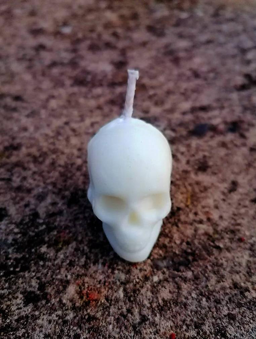 Spiritual Is soy wax Skull Candle to create the perfect mood for relaxation and spiritual healing on natural rock background