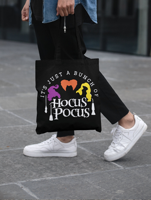Woman carrying a hocus pocus, halloween tote bag for spiritual goods and merchandise