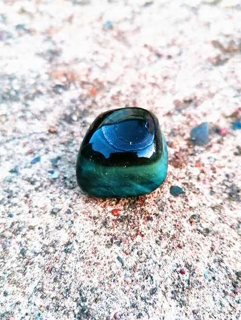 Blue Tigers Eye spiritual crystal and tumbled stone on paved holistic and natural background
