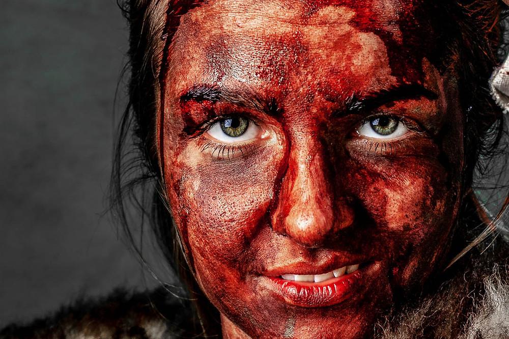 wunderschöne junge Frau mit blutverschmiertem Gesicht, verschmitztem Lächeln und atemberaubenden schönen Augen