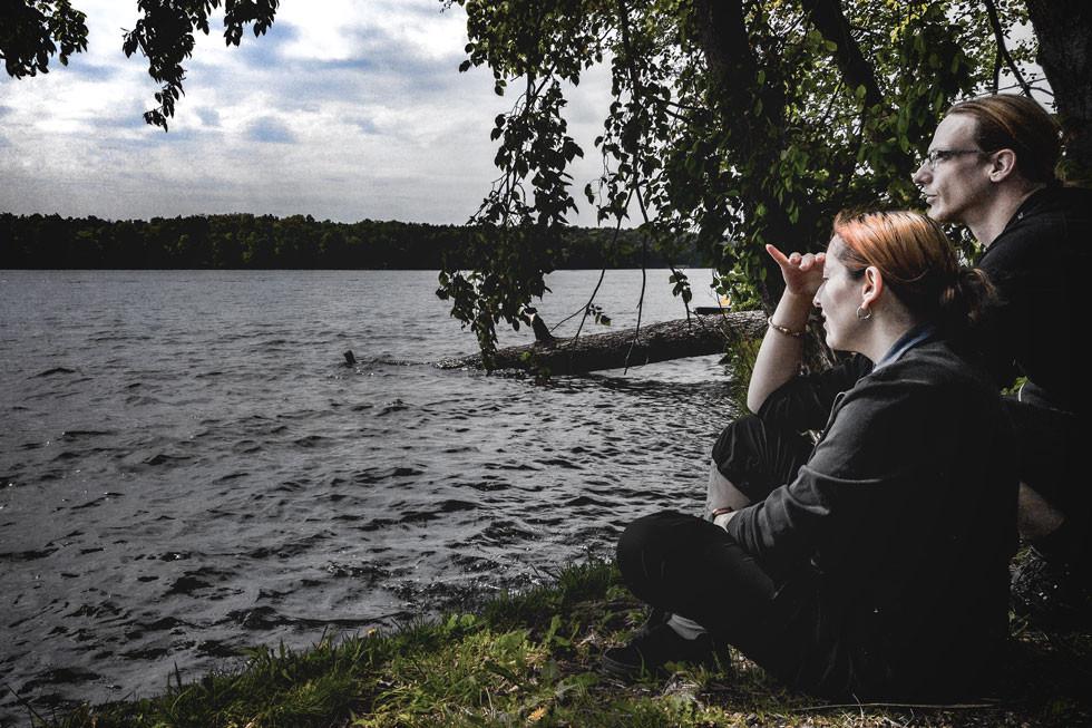 Paar sitzt am Seddiner See rothaarige junge Frau sitzt am Ufer langhaariger blonder Mann mit Brille hockt neben ihr beide blicken auf das Wasser