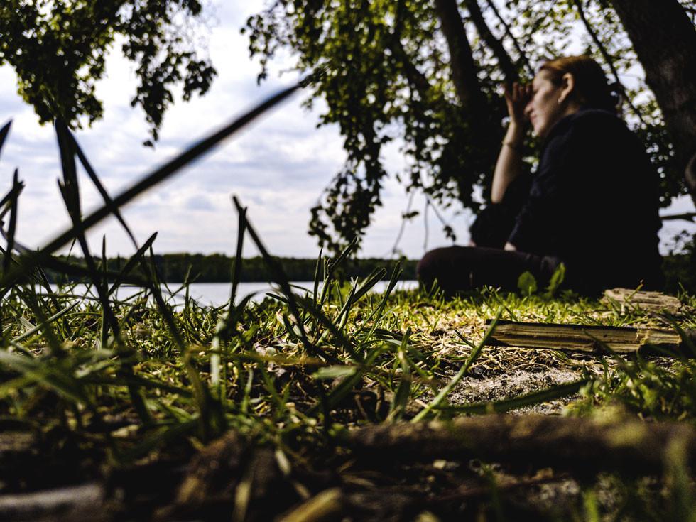 Rothaarige Frau namens Linda sitzt am Ufer des Seddiner Sees hat ihre Hand zum Sonnenschutz gehalten