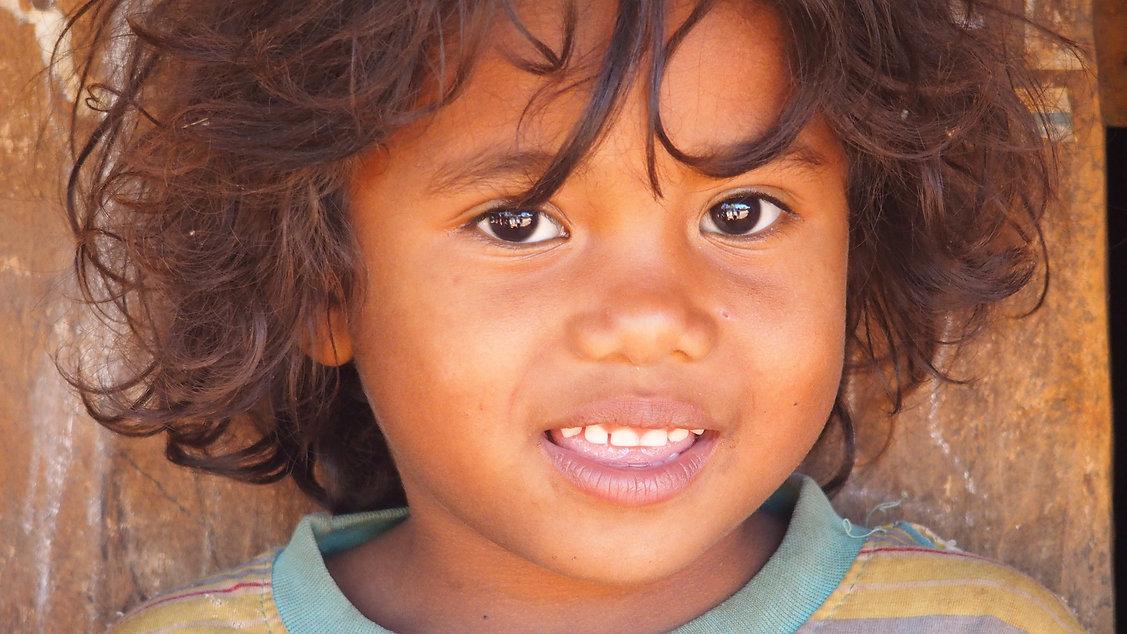 portrait d'un jeune garçon souriants aux cheveux mi-long