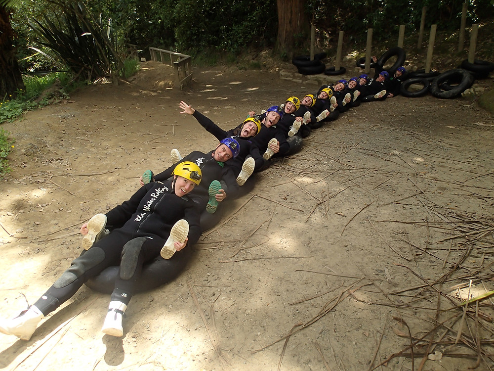 Sitting on the ground in tubes linked up like a human chain at The Legendary Black Water Rafting Company in New Zealand