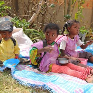 Enfants malgaches prenant leur repas en plein air