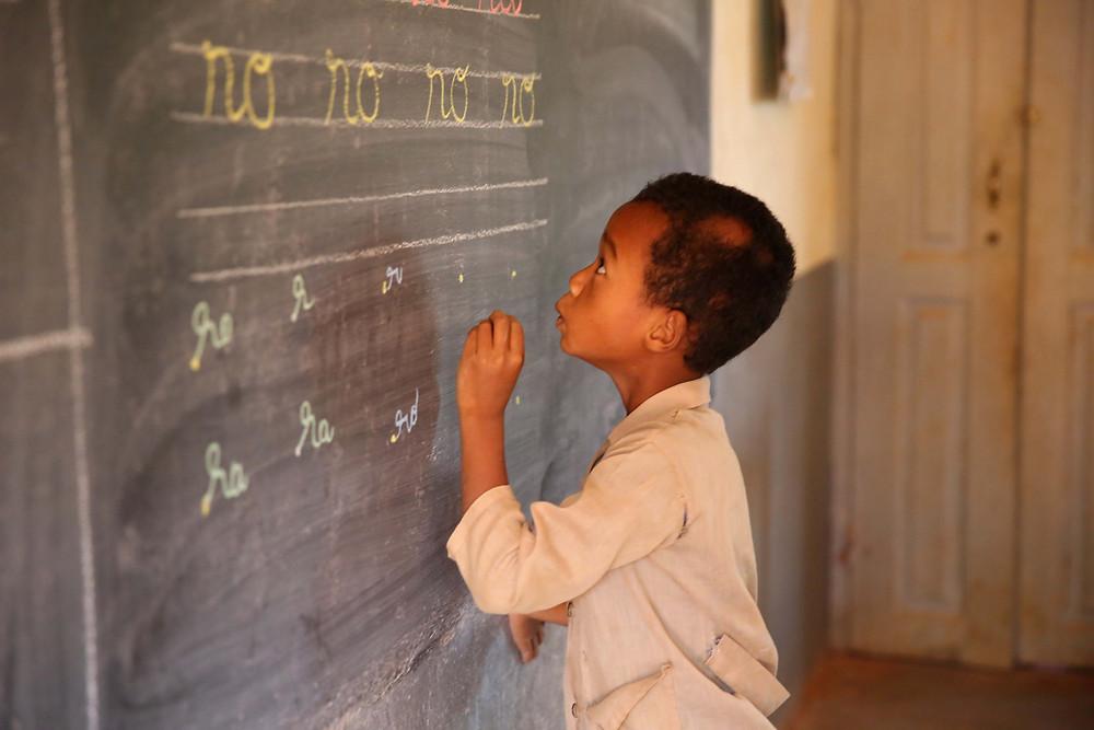 Eleve de l'école Règne en train d'écrire sur le tableau