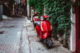 red%20motor%20scooter%20parked%20beside%