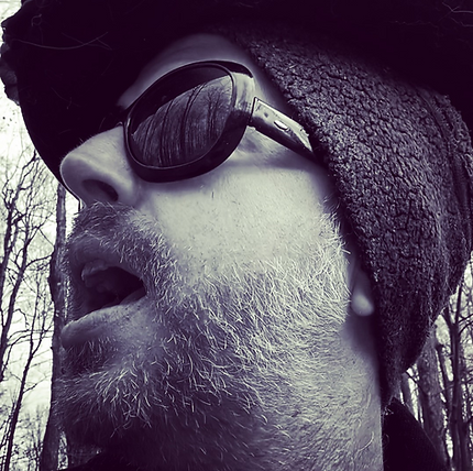 Robert German in the woods looking up while wearing oversized sun shades