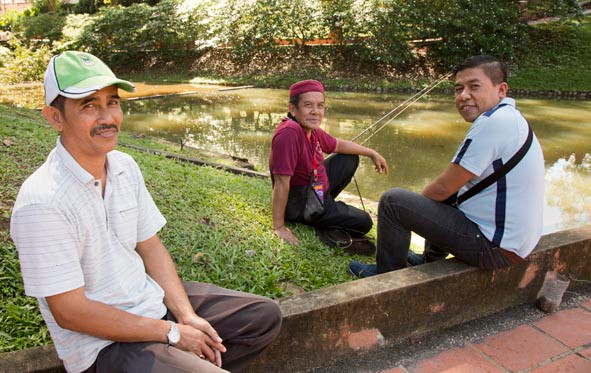 Friends Abdul Ghani, Ahmad Hashim and Mohd Azizan relax and wait for a bite on their fishing line.