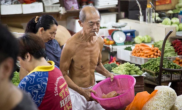 Old Chinese man smoking and sorting out vegetables