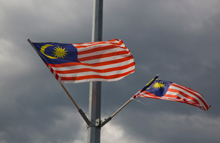 Two Malaysian flags flying with dark sky background