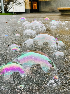 Vi leker med stora såpbubblor och ser hur färgerna skiftar.