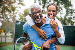 Mature couple laughing, playing tennis
