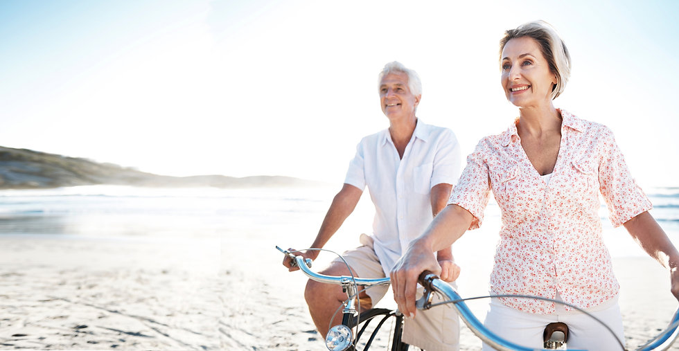 Mature couple riding bicycles on beach