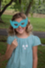 Girl holding a mask and smiling for Chateau de Sable birthday