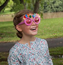 Girl wearing birthday glasses