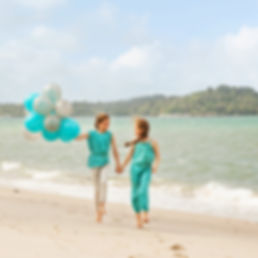 Girls walking on the beach and holding balloons