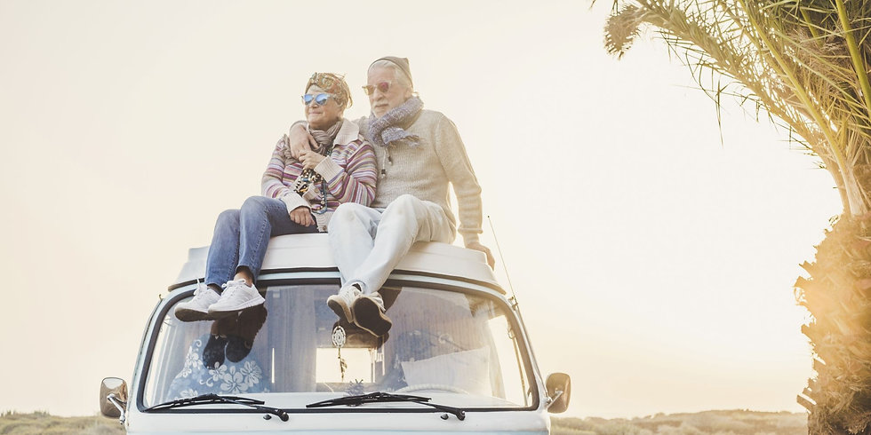 Happy retired couple sitting on the roof of a VW camper at sunset