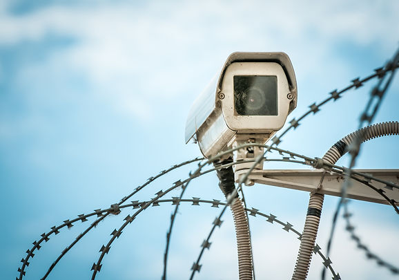 Close up view of security camera hanging among barbwire in prison or other guarded object with blue