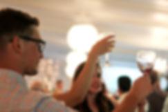 Wine glasses being raised at wedding