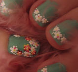 Nails painted in light green polish with white and orange floral nail stickers sealed with topcoat