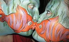 Couple painted with fish face paint design (in Cramlington) in orange, green and pink