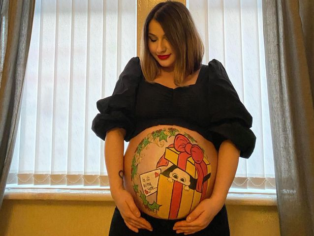 Lady's pregnant tummy painted in a Christmas present design