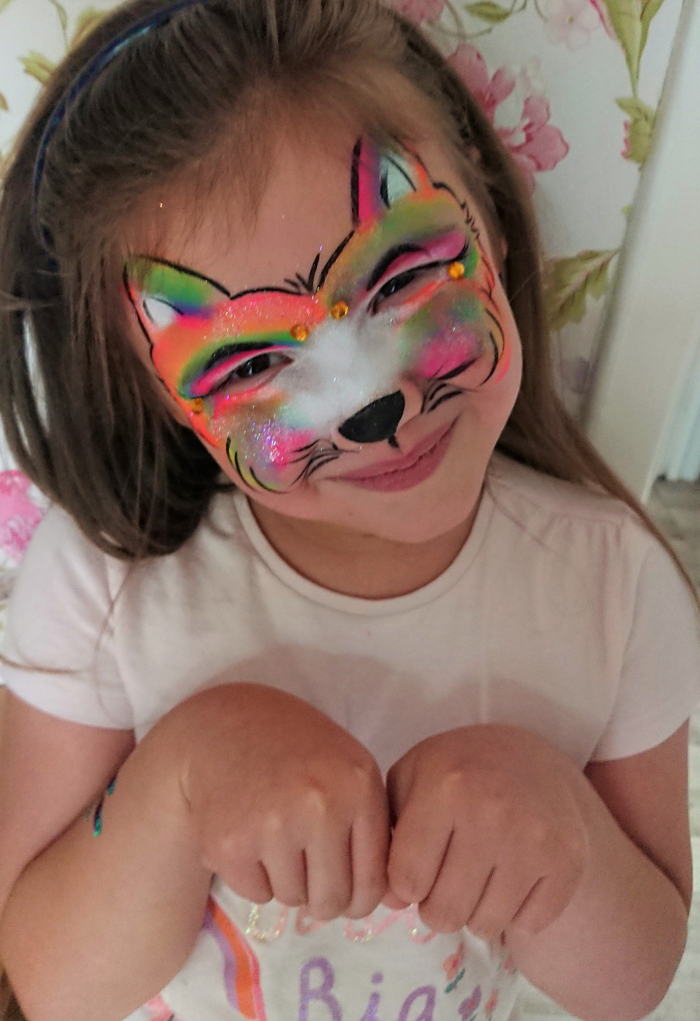 little girl with her face painted as a cat in rainbow colours