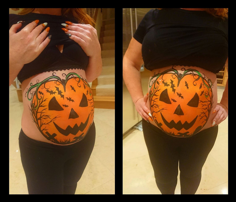 Ladies pregnant tummy painted in a pumpkin design
