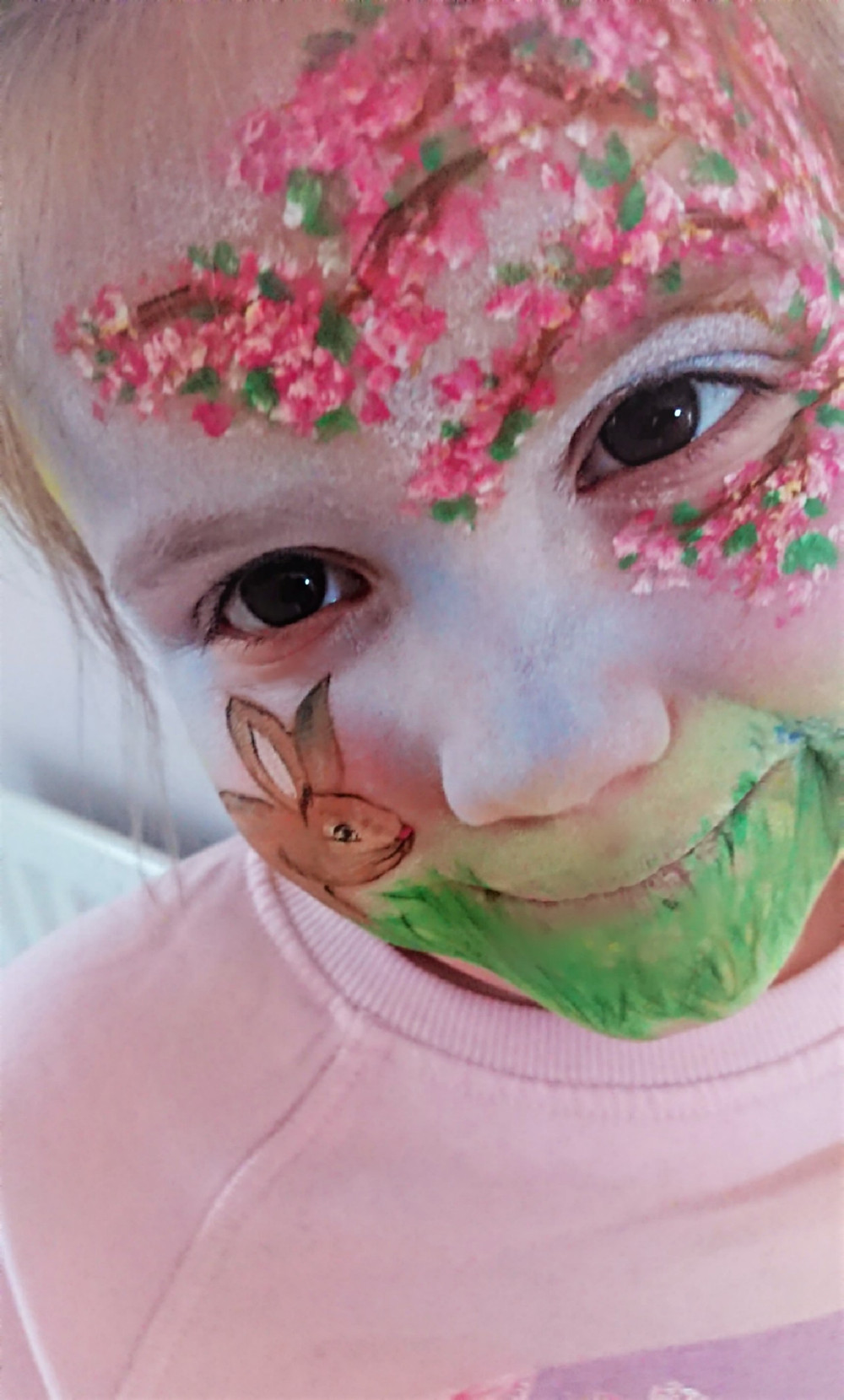 Spring face paint design including blossoms, blue skies and a bunny