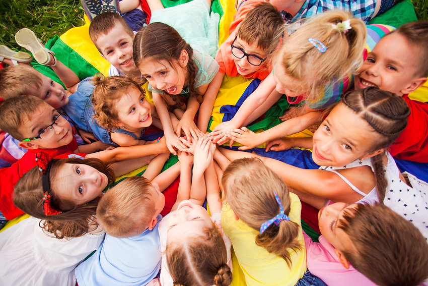 Top view kids in circle laying on colorful cloth.jpg
