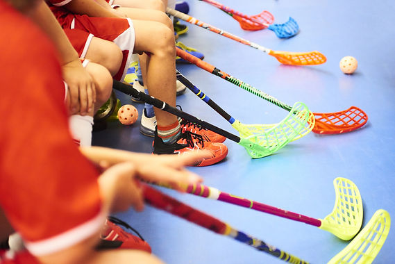 Children playing floorball. Boys holding floor ball sticks resting on the bench during a m