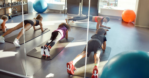Portrait of kids doing plank, exercising together with female trainer in gym. Workout on a