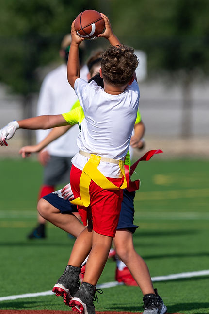 Young boy catching, running and throwing the ball in a football game.jpg