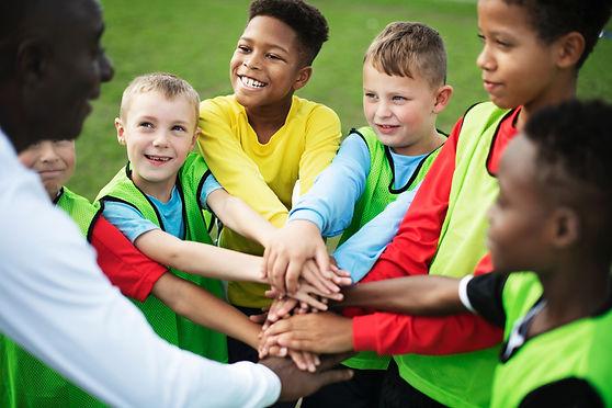 Junior football team stacking hands before a match.jpg