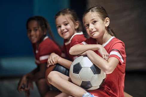 Smiling girl with soccer ball  in good mood  before training  in changing room..jpg
