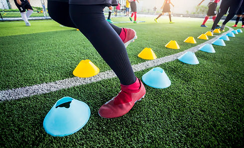 Soccer player Jogging and jump between cone markers on green artificial turf for soccer tr