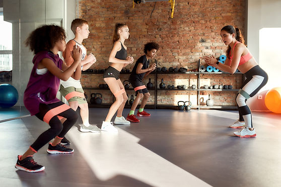 Full length shot of kids working out using resistance band in gym together with female tra