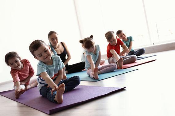 Little children and their teacher practicing yoga in gym.jpg