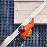 木板を持ち上げる建設作業員