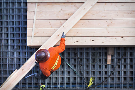 Construction worker lifting wood board