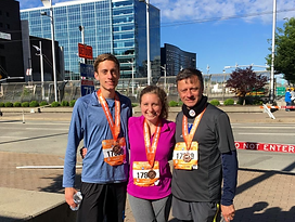 three individuals with running bibs and medals